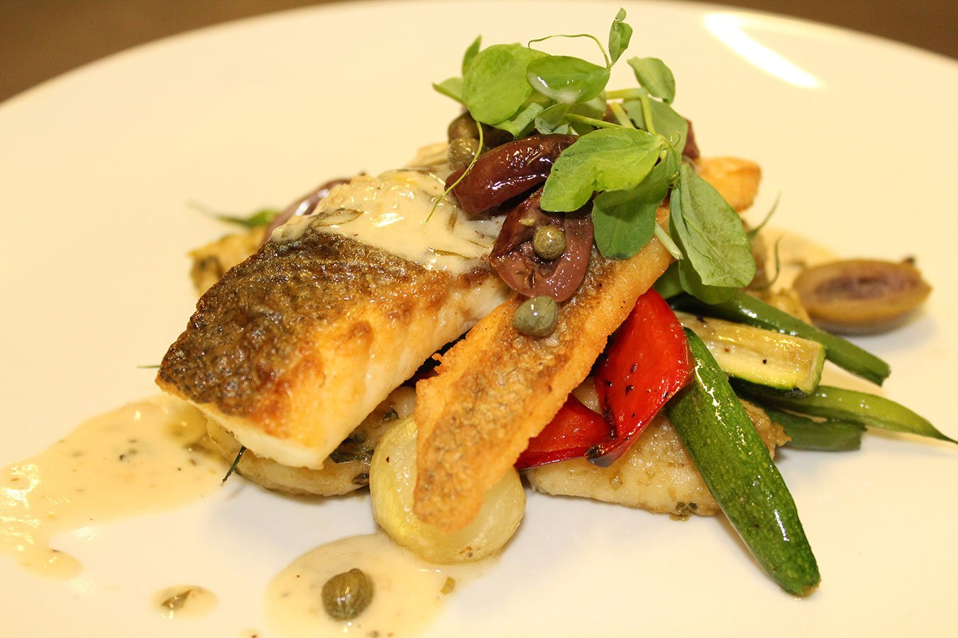 Pan Roasted Branzino with Tomato, Olive, Caper and Tarragon. Served with Pesto Gnocchi and Roasted Baby Vegetables