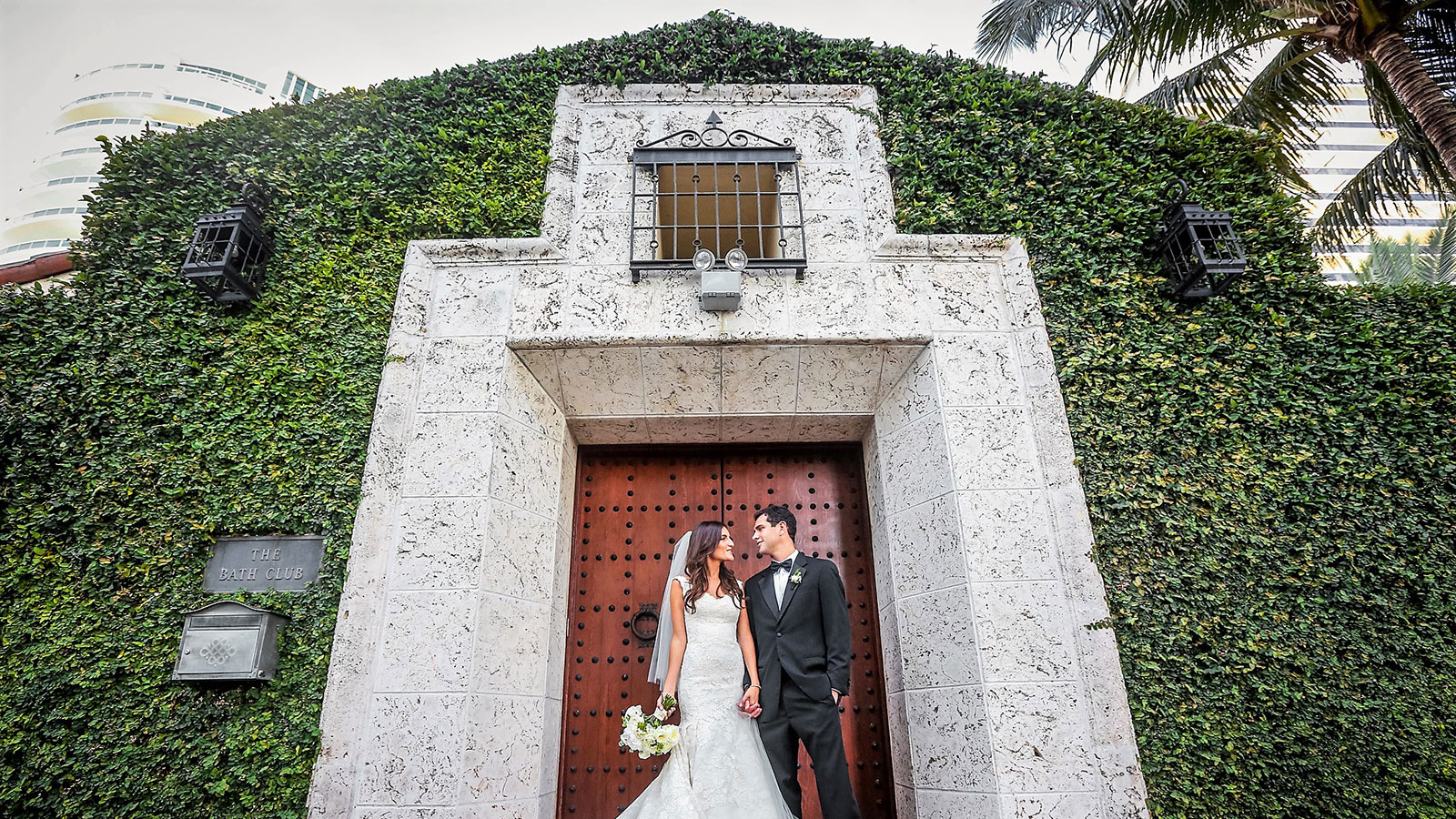 Bride and Groom at the entrance of The Bath Club in Miami Beach