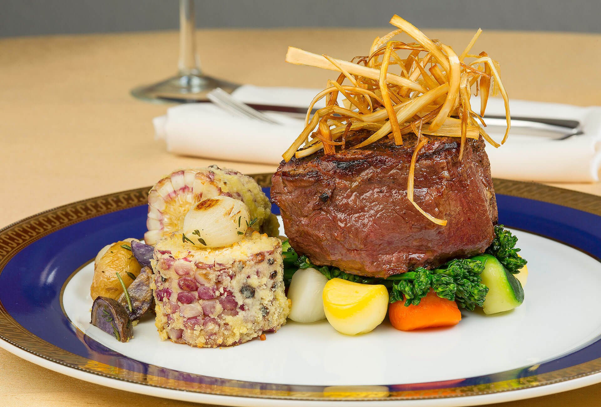 Grilled filet mignon with mexican corn on the cob, roasted rosemary peruvian and golden potatoes, deep fried leek hay, parisienne vegetables and broccoli rabe