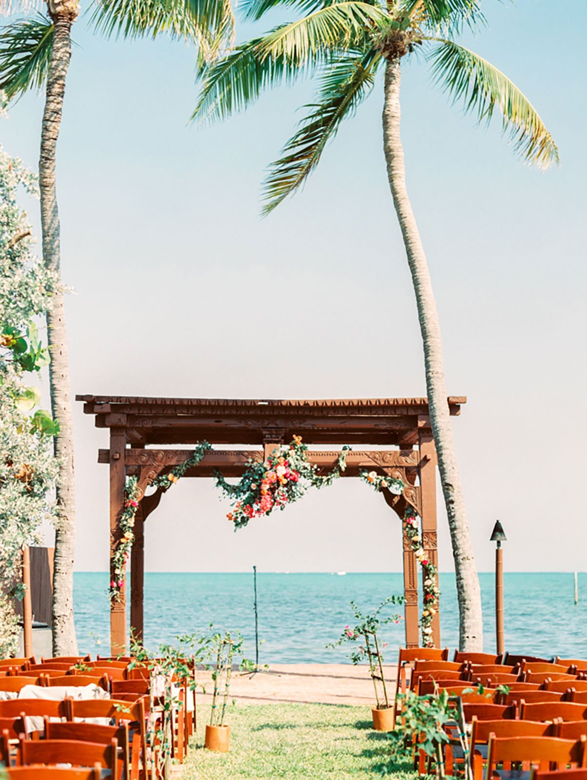 Terra-cotta pots of bougainvillea, succulents and greenery served as aisle decor at his waterfront wedding ceremony at the Caribbean Resort in Islamorada, FL