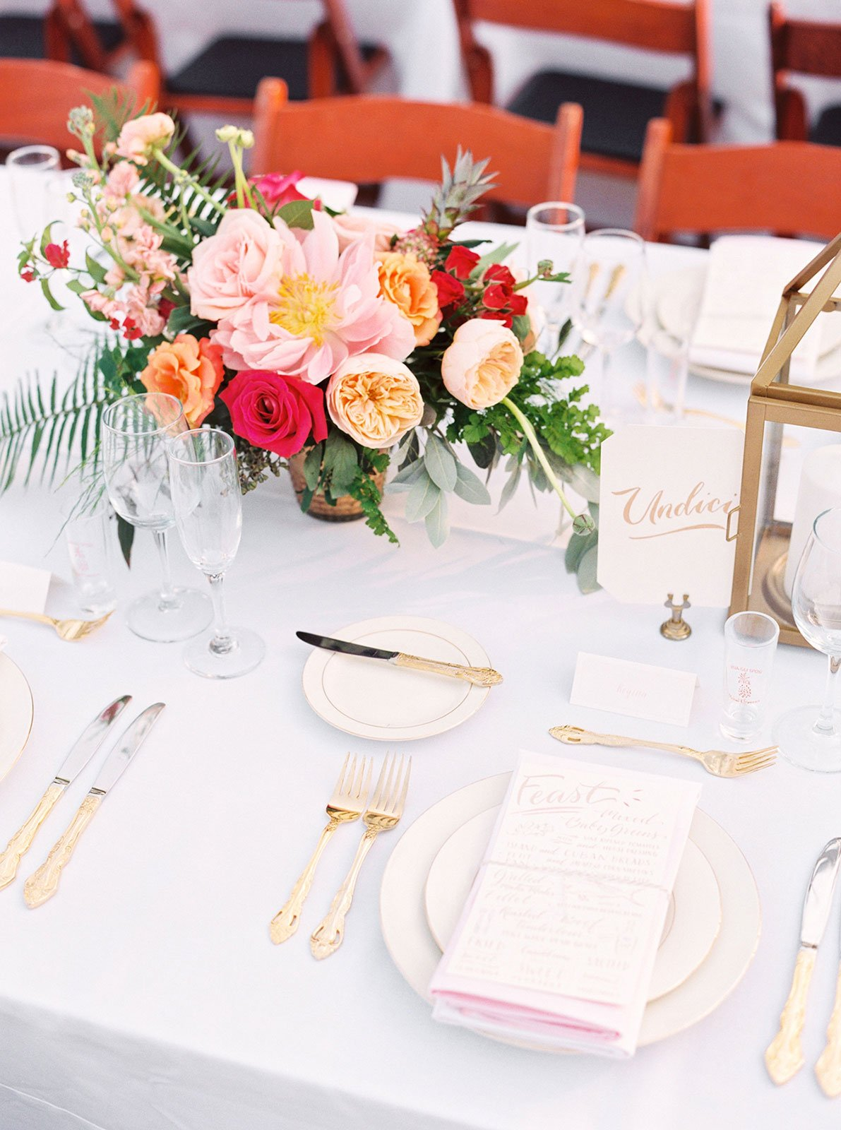 Family-style tables were set with white linens, pink ombre napkins and gold silverware at this destination wedding in Islamorada, FL