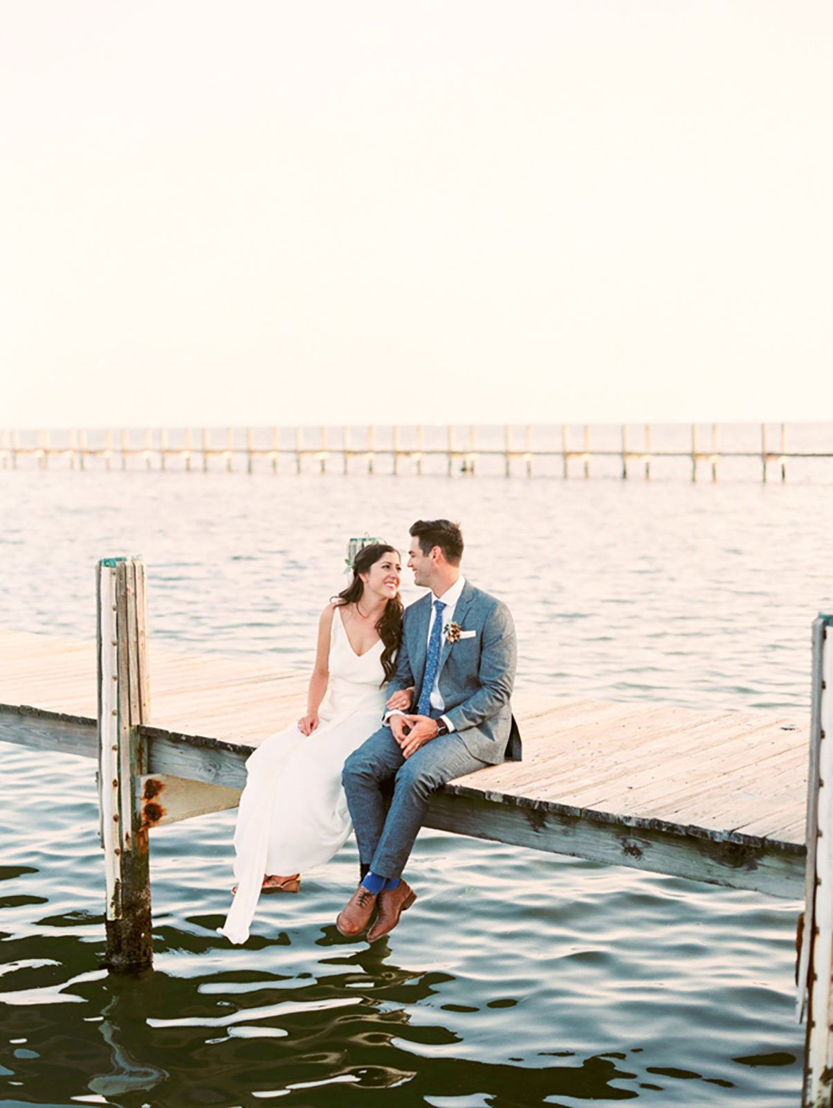 Bride and Groom enjoy a quiet moment on dock of at their waterfront wedding the Caribbean Resort in Islamorada, FL