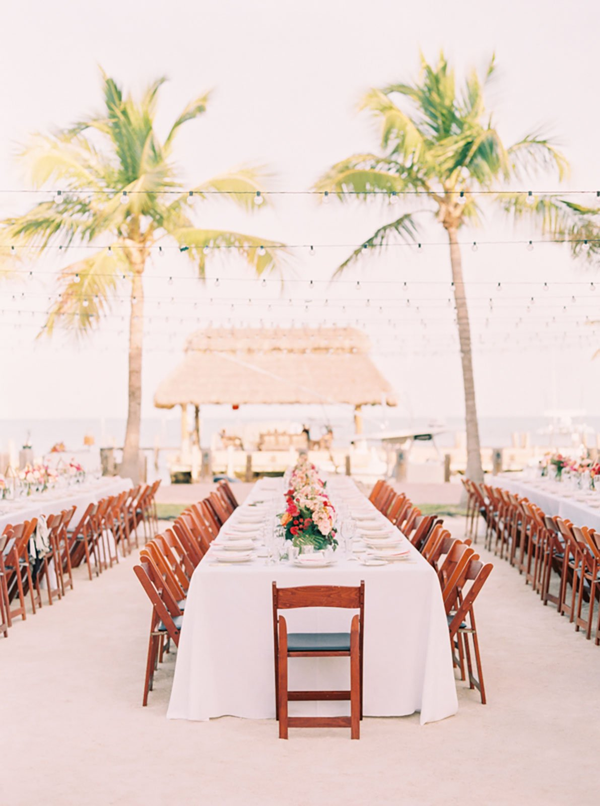 Bright waterfront wedding reception centerpieces gave the table settings a pop of color at this destination wedding
