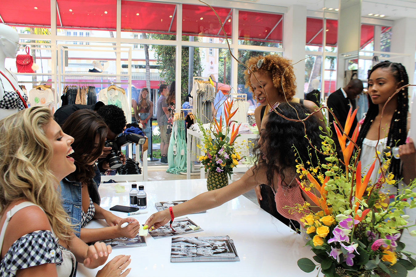 Tasha Oakley and Devin Brugman autograph posters for fans at GUESS Lincoln Road store event to promote their 2017 swimsuit collection