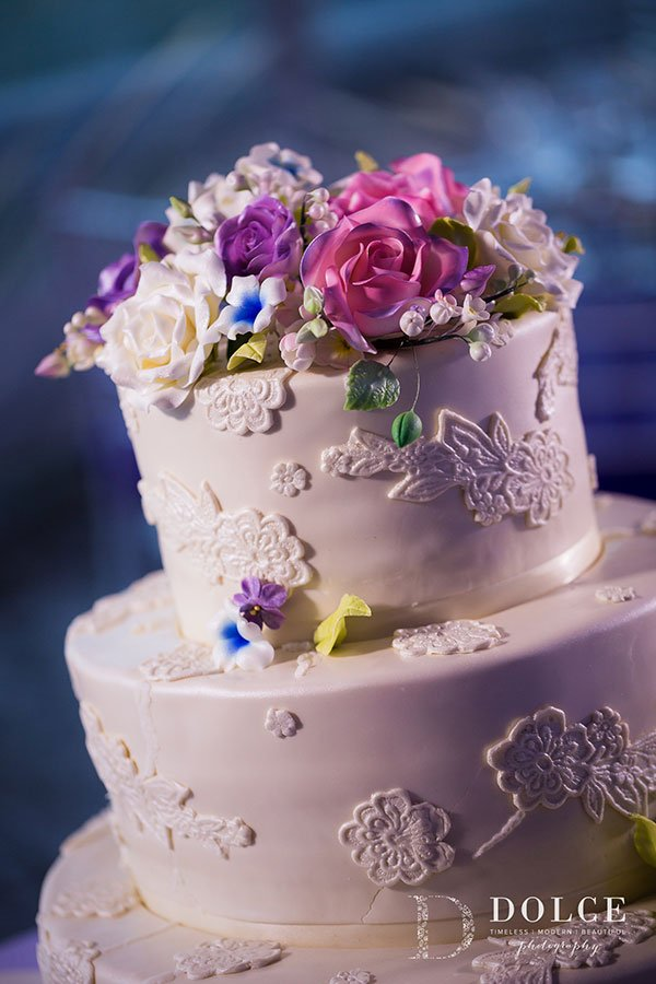 Wedding Colors 2018 | Delicate ultra violet and pink sugar flowers accent the ivory wedding cake