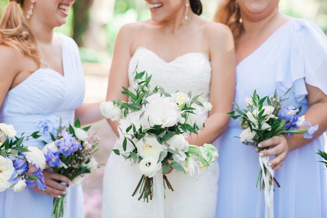 Iris flowers are mixed in with pale peonies, ranunculus and anemones in bridesmaids bouquets