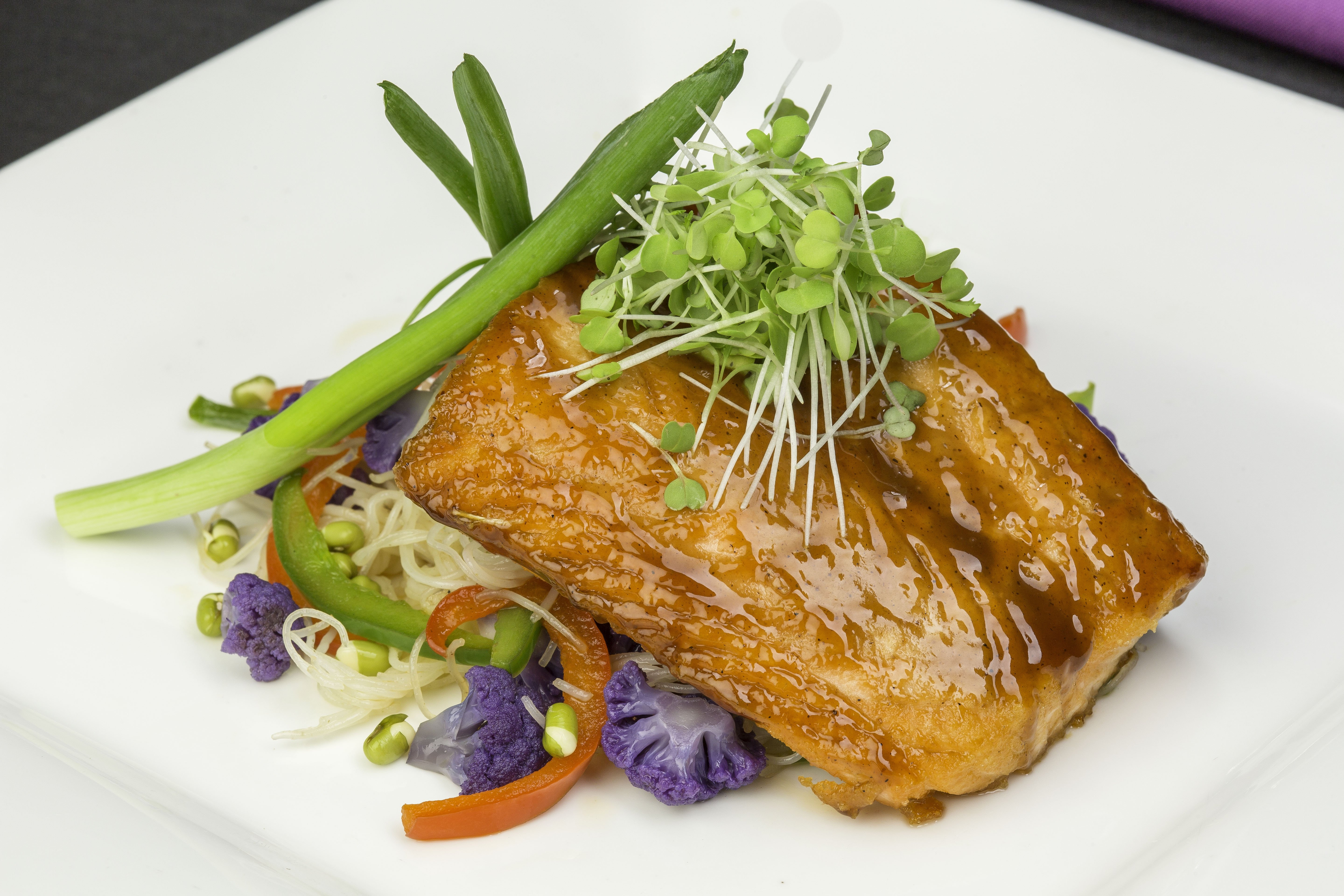 Korean barbequed salmon filet with rice noodles, purple cauliflower and micro greens