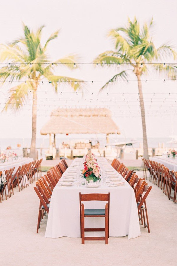 Beach wedding mimics the soft hues of Living Coral wedding color palette